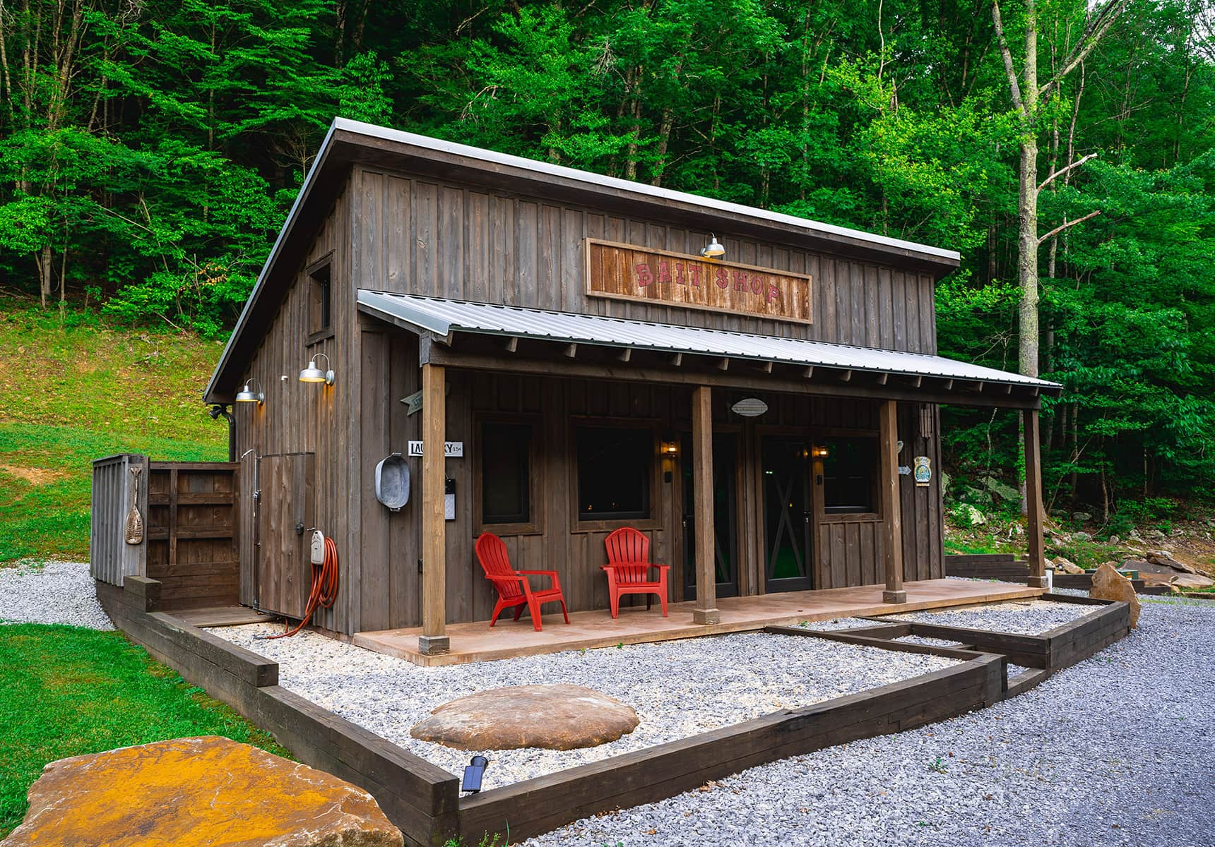 Exterior front view of the Baitshop Cabin with a gravel landing area and an outdoor shower