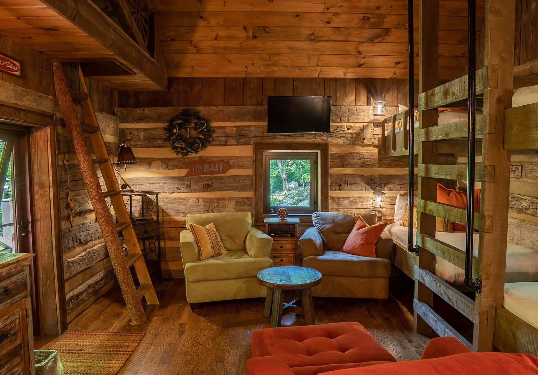 Fishing Creek Cabin living room with several couches and ladder to the loft sleeping area
