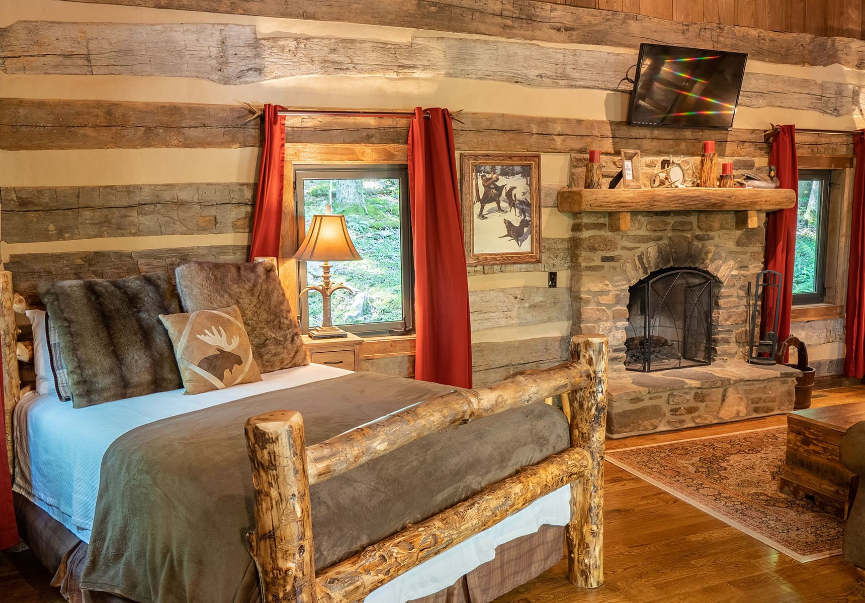 Wilderness Lodge bed with a stone fireplace and wood floors - Monroe County