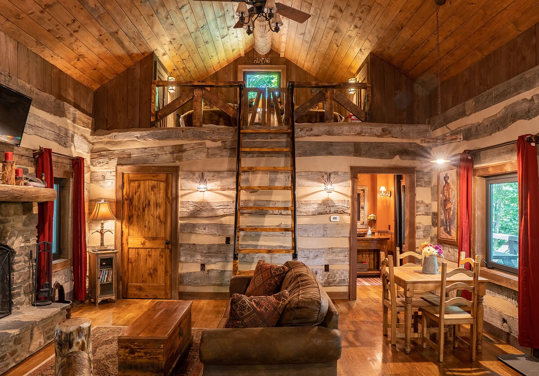 Wilderness Lodge interior living space with a sleeper sofa and a loft accessible by a wide ladder - West Virginia Cabin