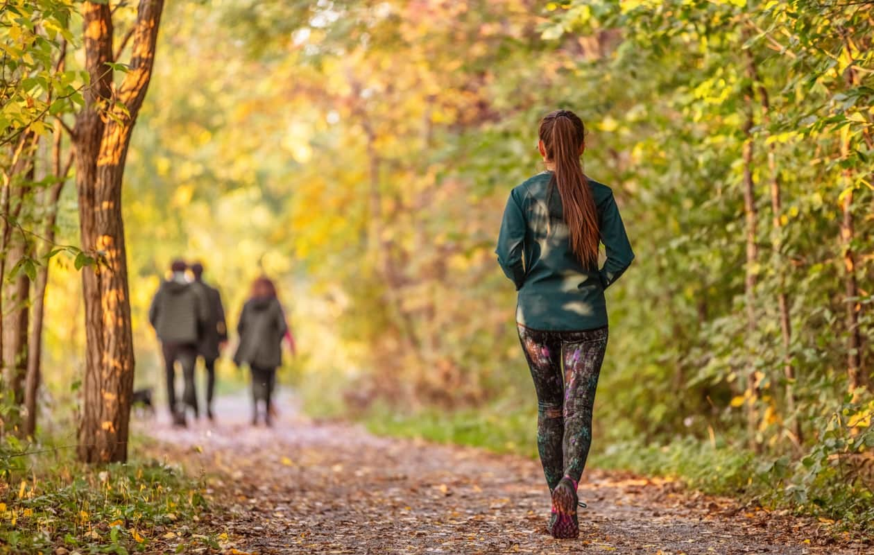 Woman walks on a trail in the woods