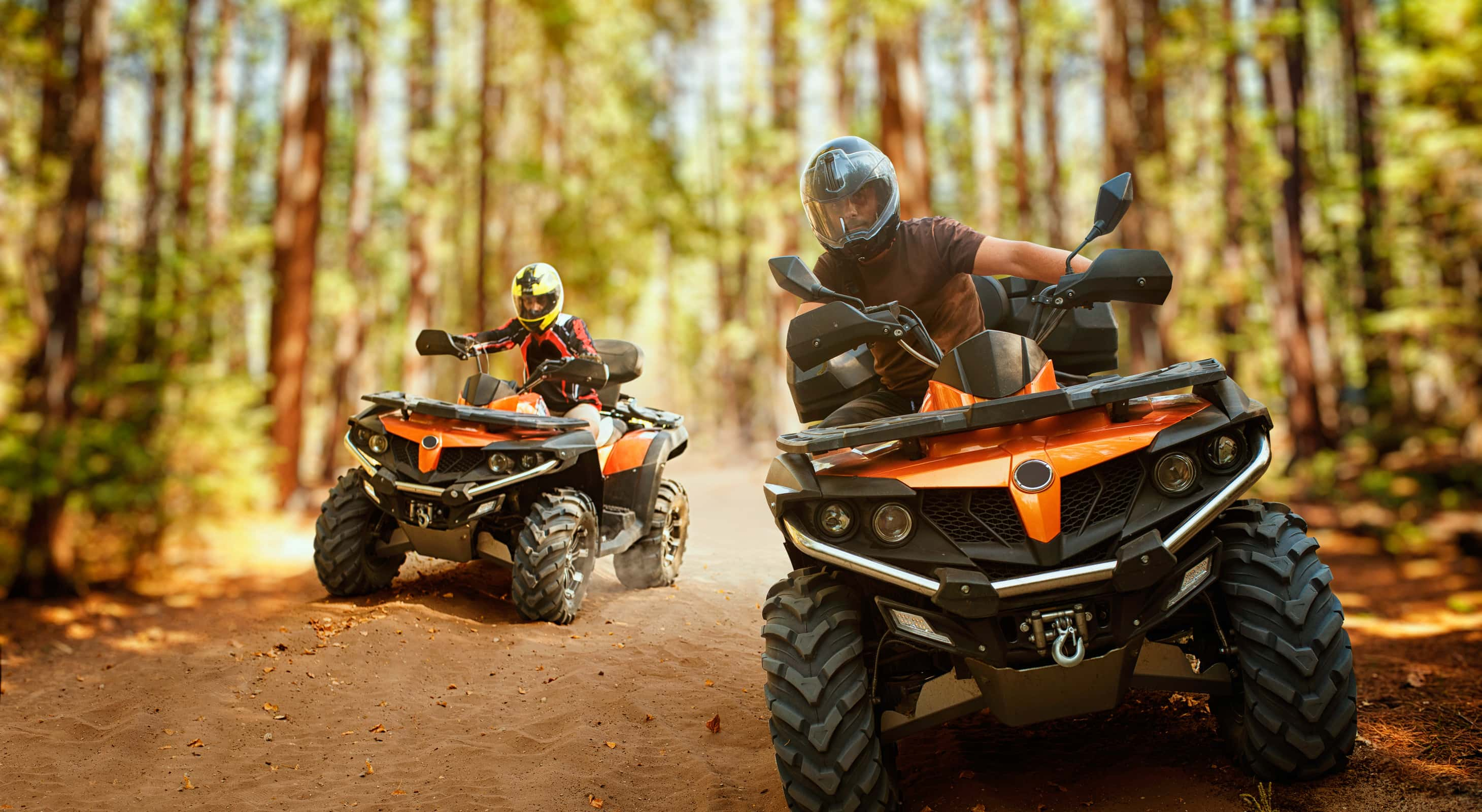 Two people riding ATVs on a trail in the woods