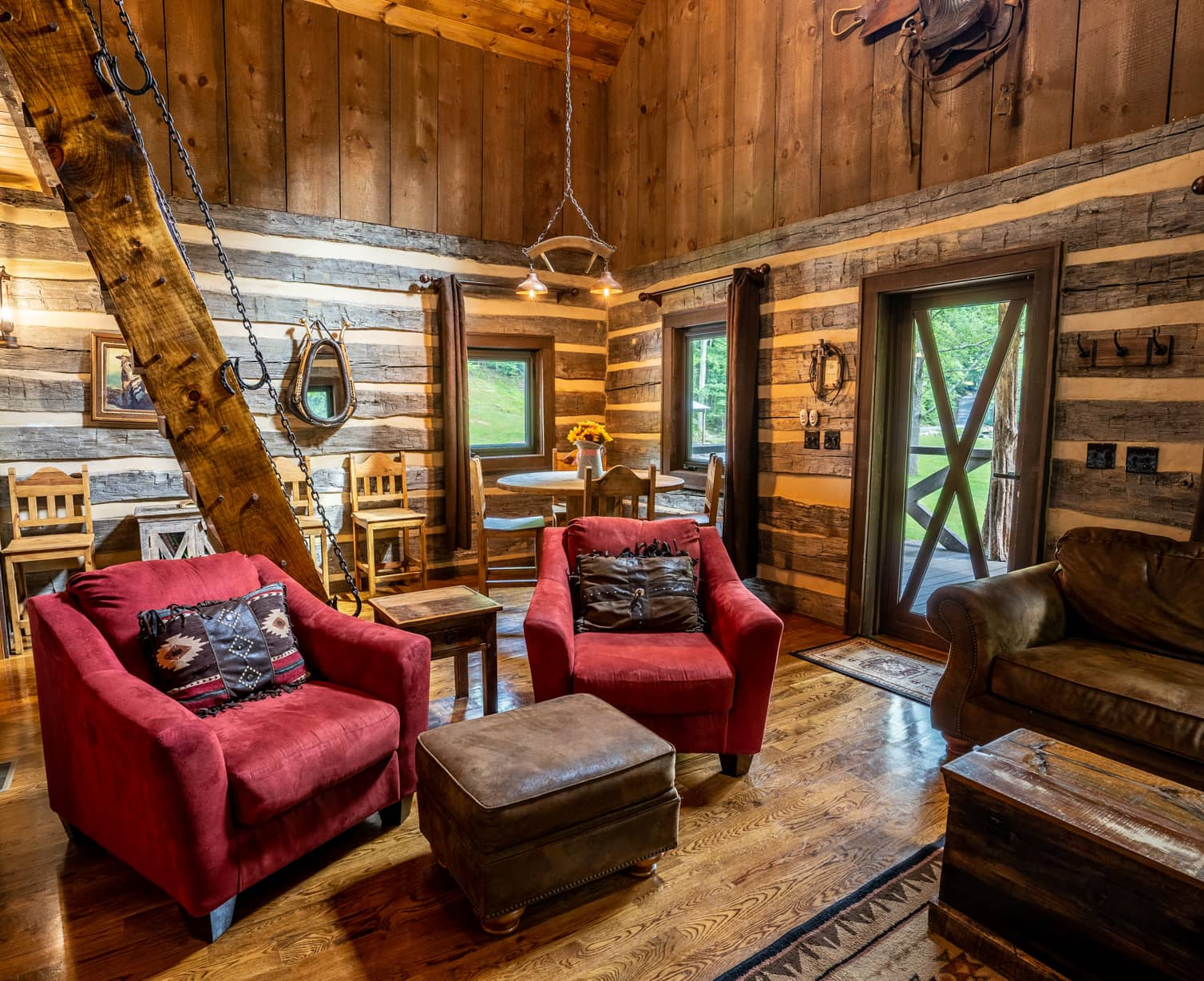 Cowboy cabin living room with ample seating, a dining table, and wide ladder leading to the loft