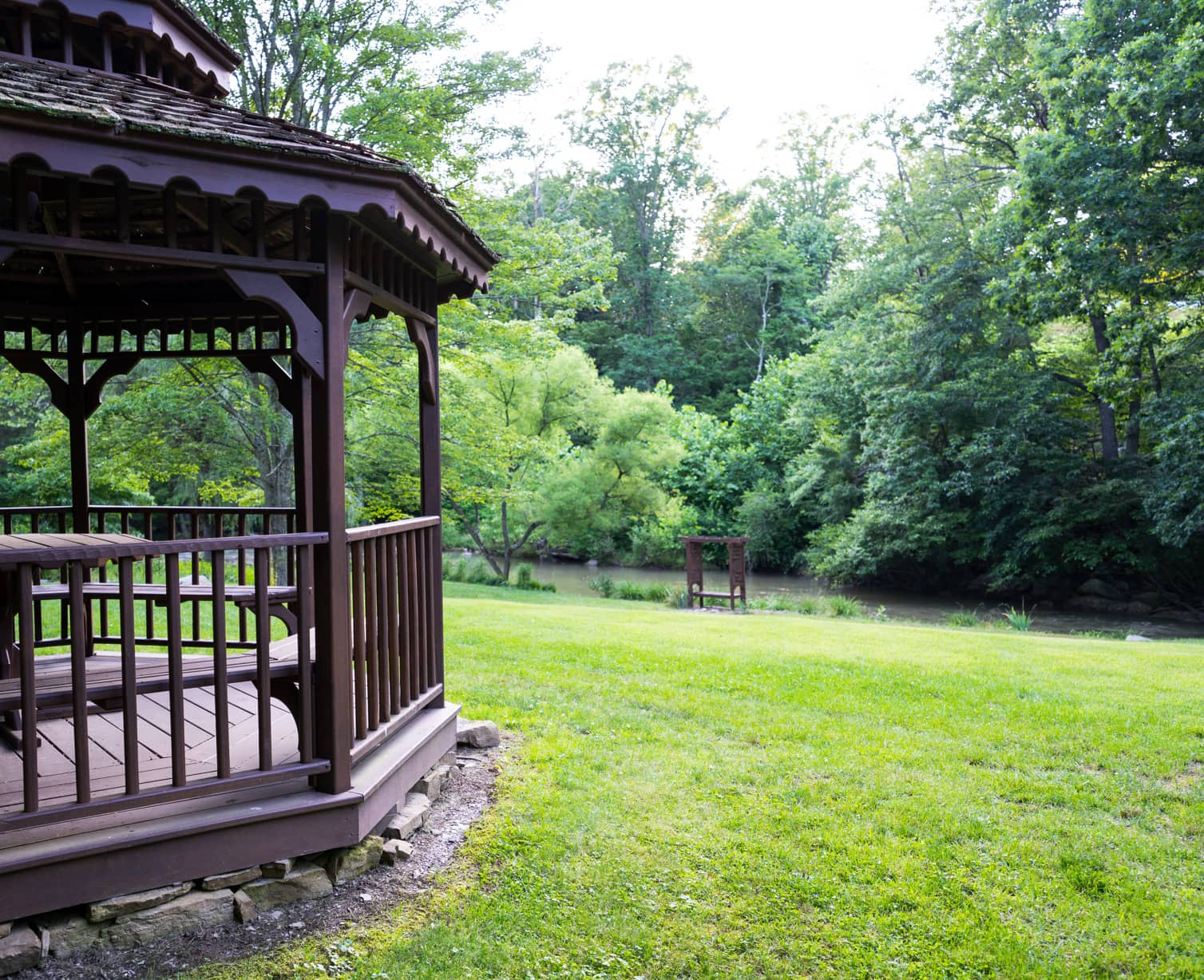A wooden gazebo overlooking a creek