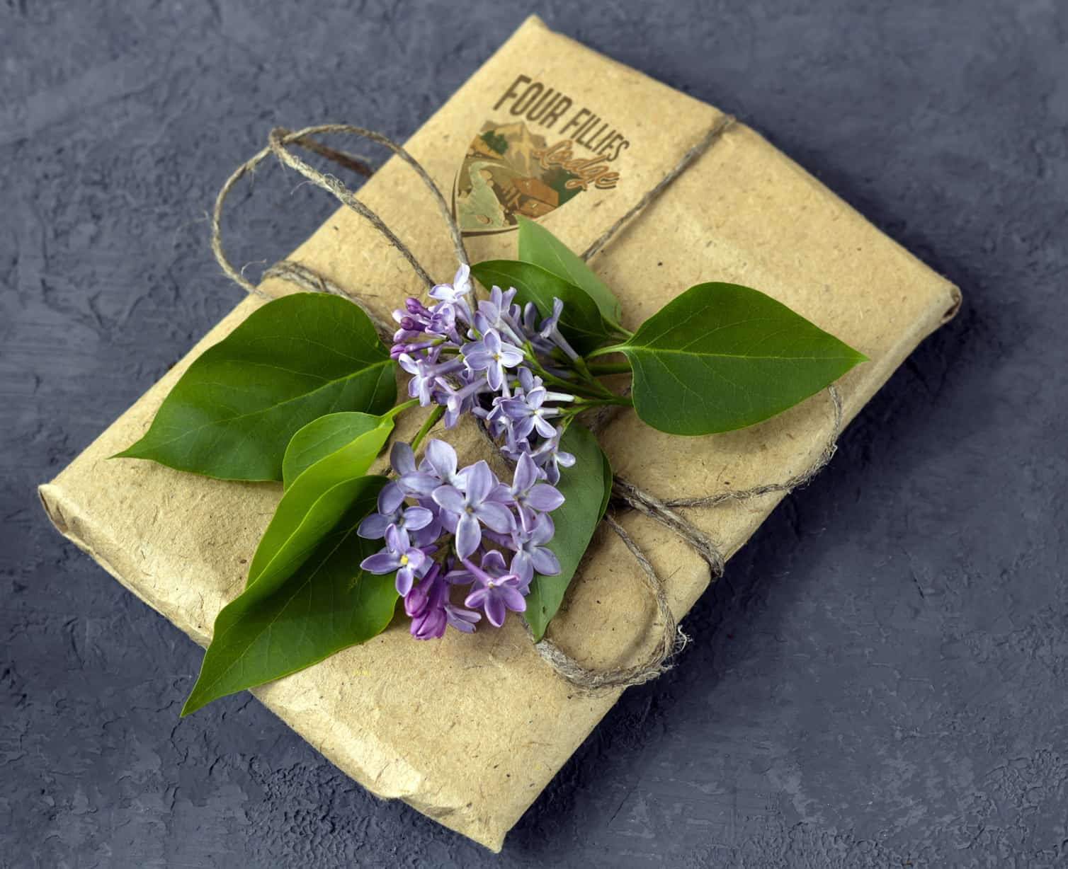 A small craft paper package tied with twine and small purple flowers