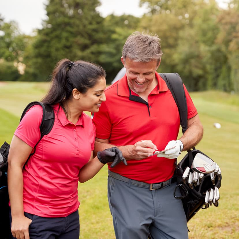 A man and a woman checking their scores while golfing