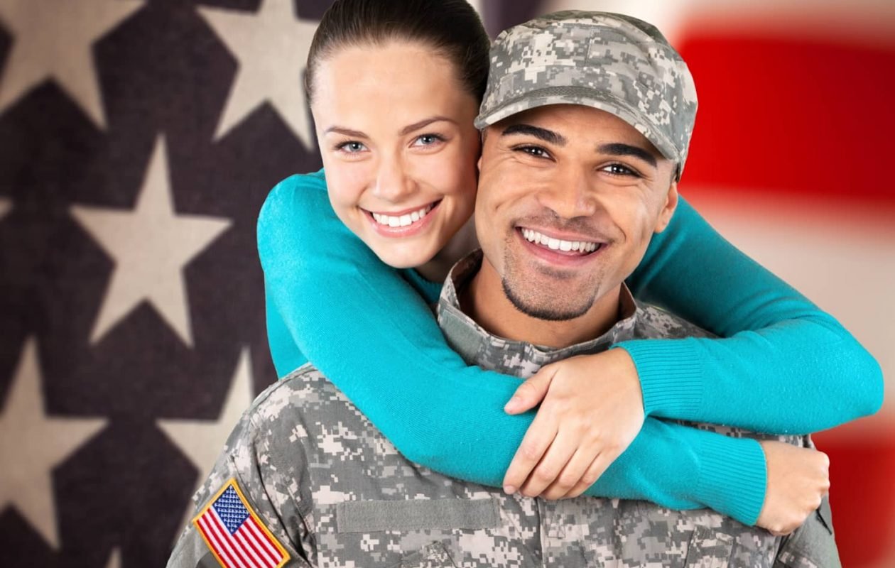 Active duty military member and his partner in front of an American flag background