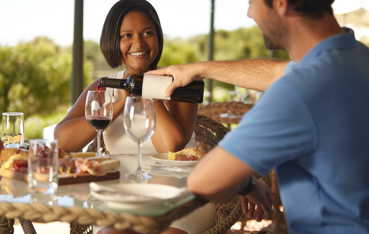 A man pours a glass of wine to a woman