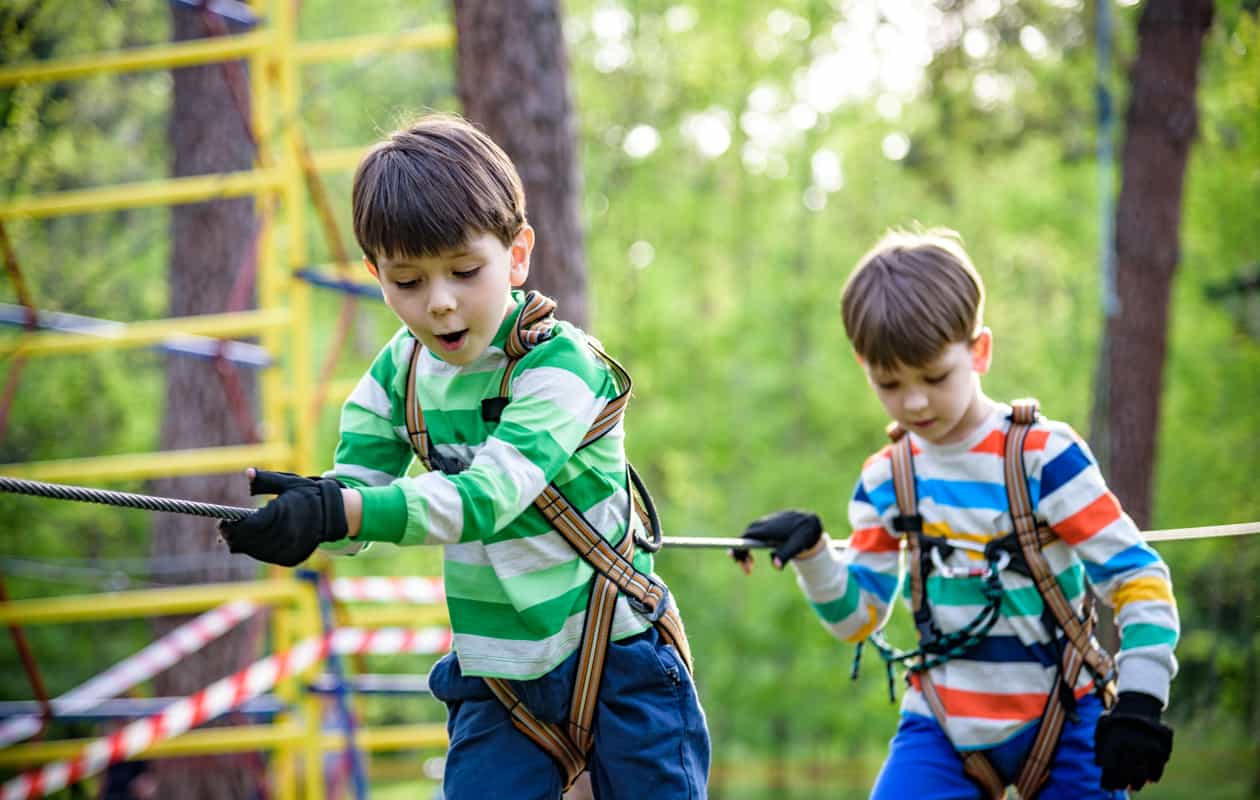 Two twin brothers walk across a bridge at a zipline attraction